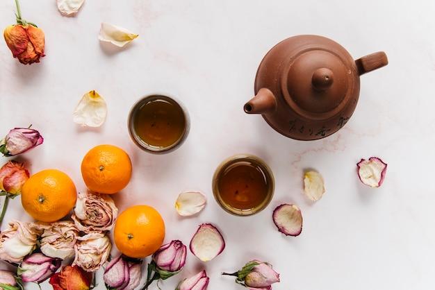 Un'arancia e una rosa secca con tisana in teiera e tazze da tè