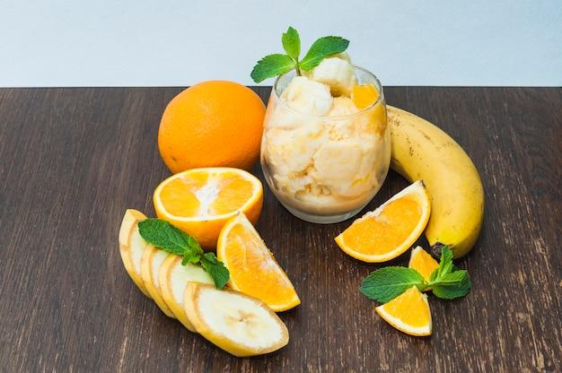 Un'arancia; gelato alla banana su fondo strutturato di legno contro fondo blu