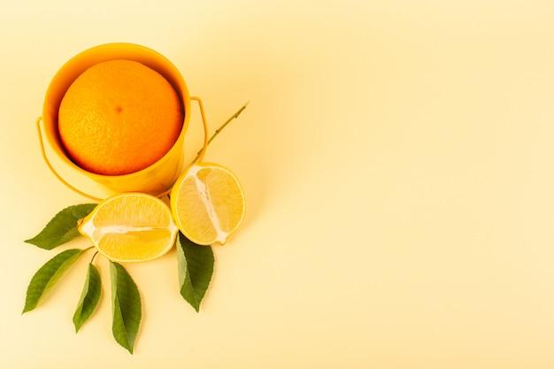 Un'arancia intera di vista frontale dentro il canestro arancio insieme al limone succoso fresco maturo maturo affettato isolato sull'arancia degli agrumi del fondo crema