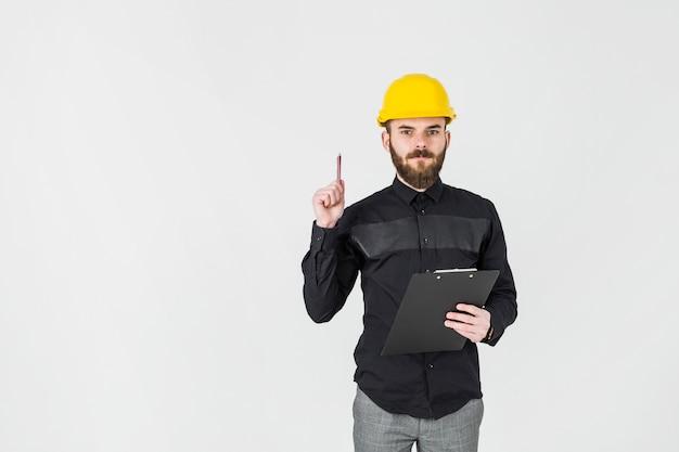 Un architetto che indossa la lavagna per appunti della tenuta dell'elmetto protettivo sopra fondo bianco