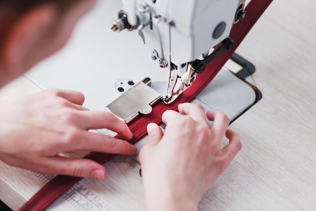 Un artigiano di pelletteria produce articoli di pelletteria su una macchina da cucire nel suo negozio.