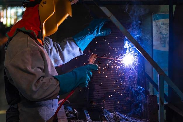 Un artigiano sta saldando con il pezzo in acciaio. persona che lavora sul saldatore in acciaio.