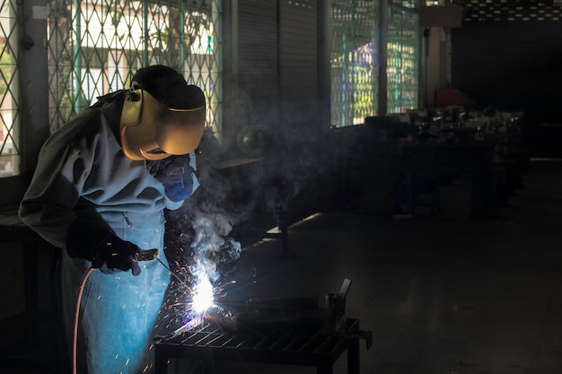 Un artigiano sta saldando con l'acciaio del pezzo da lavorare. persona che lavora a proposito dell'acciaio del saldatore usando la saldatrice elettrica ci sono linee di luce che escono e attrezzature di sicurezza nell'industria di fabbrica.
