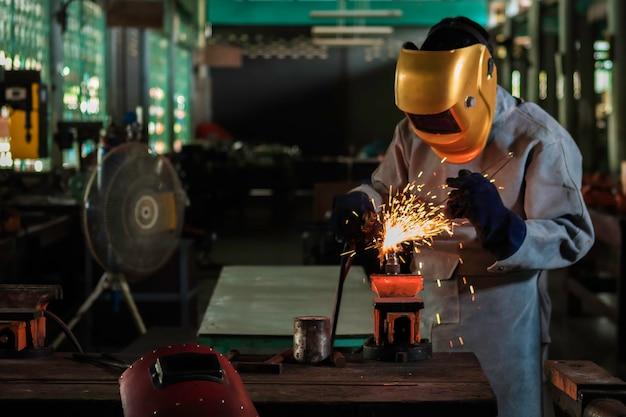 Un artigiano sta saldando con l'acciaio del pezzo in lavorazione.