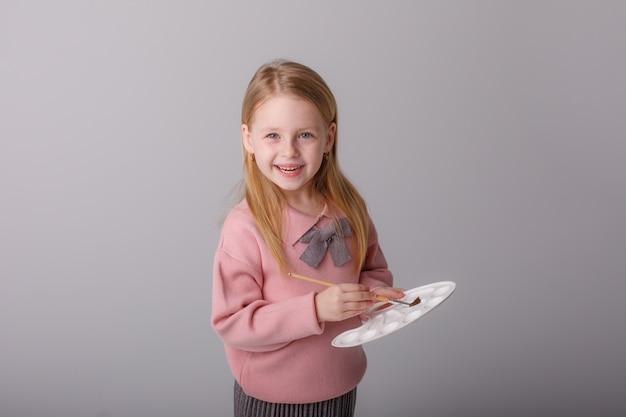 Un artista bambino tiene un pennello e una tavolozza su uno spazio grigio