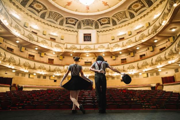Un artista di due mime che si piega sul palco nell'auditorium