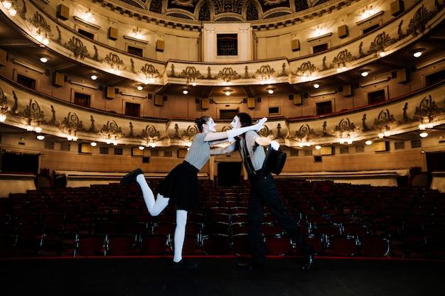 Un artista di due mimi esibirsi sul palco in un auditorium vuoto