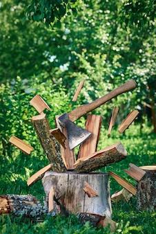 Un'ascia taglia un ceppo in piedi su un vecchio moncone, le schegge volano in diverse direzioni