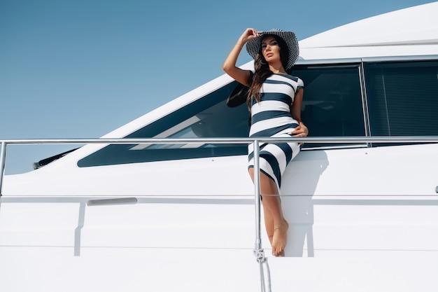 Un aspetto caucasico ragazza modello con il trucco in un vestito a strisce e cappello in piedi yacht yacht. viaggia in paesi caldi. avvicinamento