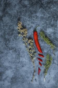 Un assortimento di peperoncino rosso con timo e rosmarino su una superficie scura in verticale