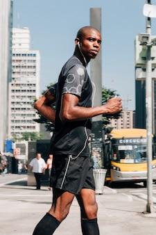 Un atleta maschio fiducioso misura il giovane che pareggia sulla strada che ascolta la musica sul trasduttore auricolare