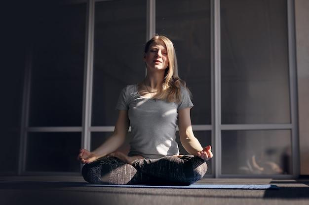 Un'attraente ragazza bionda in abiti sportivi medita durante le lezioni di yoga. il concetto di uno stile di vita sano. vista frontale