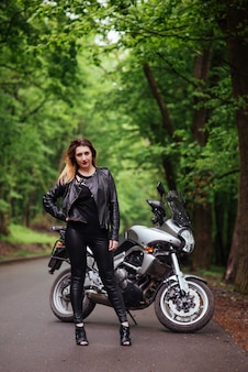 Un'attraente ragazza sexy vestita di pelle in posa vicino a una moto sportiva all'esterno