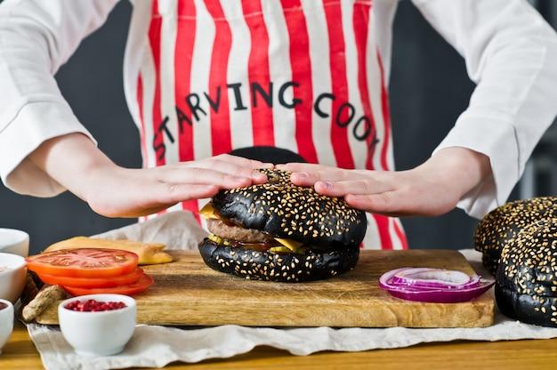 Un attraente ragazzo dai capelli rossi nel grembiule di uno chef sta cucinando un hamburger in cucina. ricetta per cucinare cheeseberger nero. hamburger fatto in casa succosa.