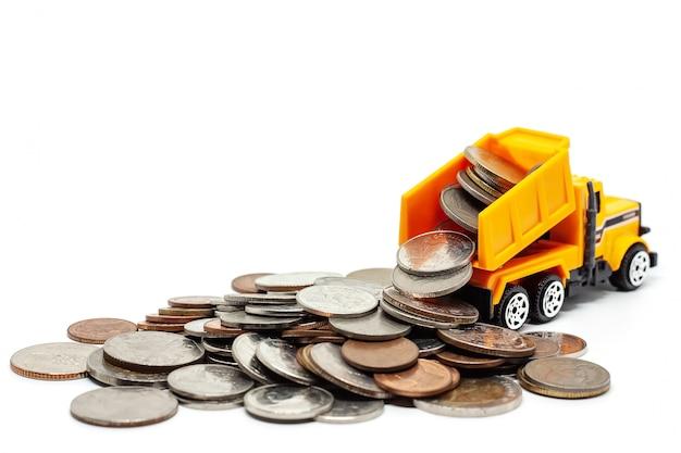 Un autocarro con cassone ribaltabile giallo del giocattolo con il mucchio delle monete su bianco