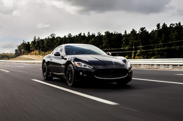 Un'automobile coupé sportiva nera guida sull'autostrada.