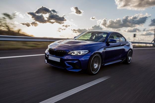 Un'automobile di berlina blu che guida sulla strada in un tempo nuvoloso.