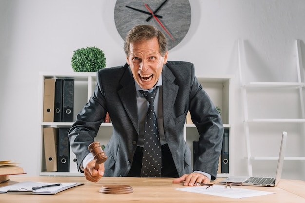 Un avvocato maturo arrabbiato che colpisce il maglio sul blocco sonoro nell'aula di tribunale