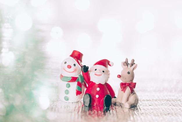 Un babbo natale in miniatura con le sue renne e pupazzo di neve sullo sfondo di natale. natale greeti