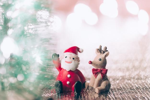 Un babbo natale in miniatura con le sue renne sullo sfondo di natale. biglietto di auguri di natale