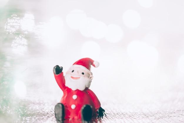 Un babbo natale in miniatura su sfondo di natale. cartolina d'auguri di natale con lo spazio della copia.