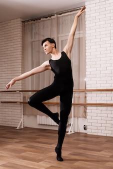 Un ballerino maschio che prova in una classe di balletto.
