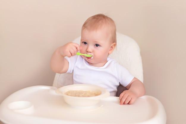 Un bambino allegro mangia la farina d'avena con un cucchiaio