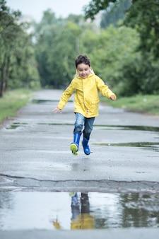 Un bambino bagnato sta saltando in una pozzanghera.