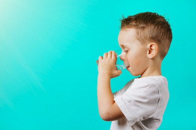 Un bambino beve acqua su uno sfondo turchese