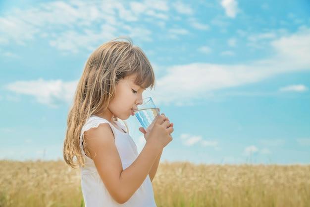 Un bambino beve acqua sullo sfondo del campo