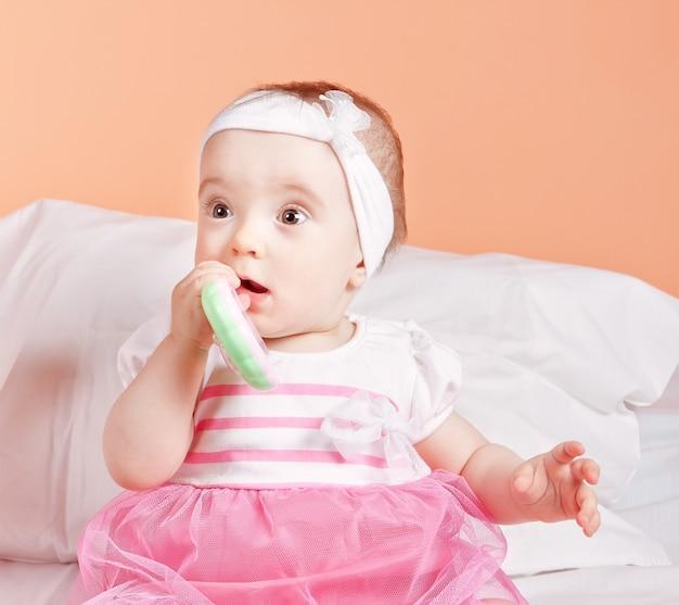 Un bambino carino e adorabile gioca un giocattolo un anno. in un bellissimo vestito.