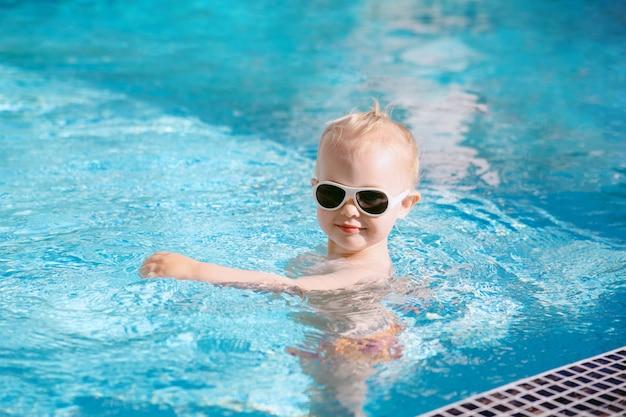 Un bambino carino in piscina.