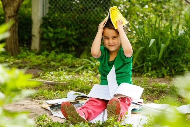Un bambino carino sta leggendo nel parco.