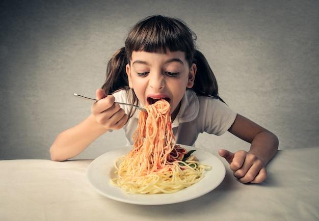 Un bambino che mangia pasta