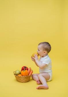 Un bambino con un cesto di frutta e verdura su uno spazio giallo. il bambino si siede lateralmente e mangia un limone. orientamento verticale. copia spazio