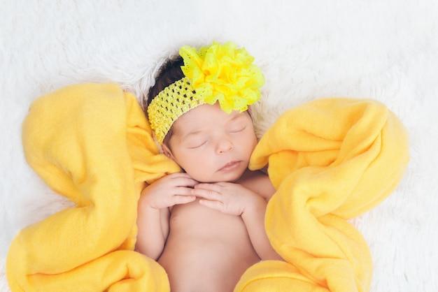 Un bambino con una benda gialla con un fiore in testa in una coperta gialla a forma di fiore