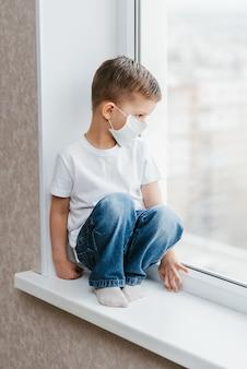 Un bambino con una mascherina medica è seduto a casa in quarantena a causa del coronavirus e della covide -19 e guarda fuori dalla finestra.
