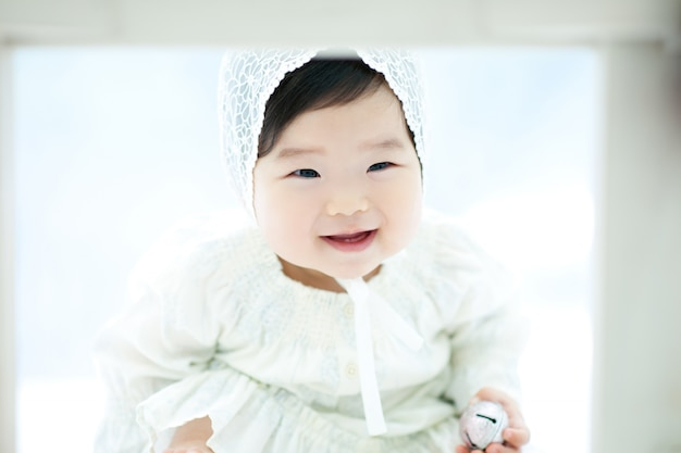 Un bambino con uno sfondo bianco e un cappello bianco sta giocando.