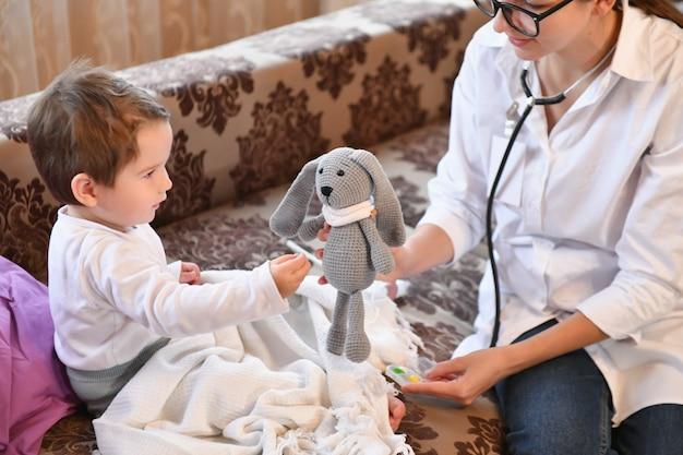 Un bambino dà le pillole a un giocattolo con un medico