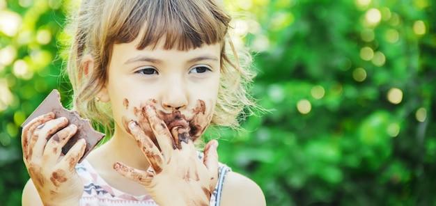 Un bambino dai dolci denti mangia cioccolato. messa a fuoco selettiva