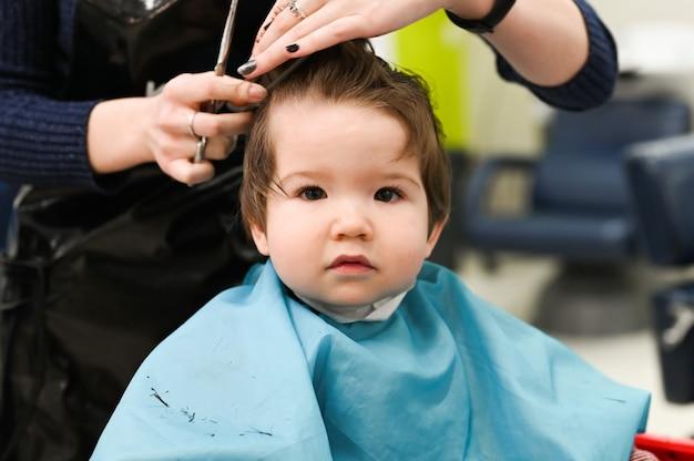 Un bambino dal parrucchiere. il primo taglio di capelli del bambino dal parrucchiere. taglio di capelli del bambino.