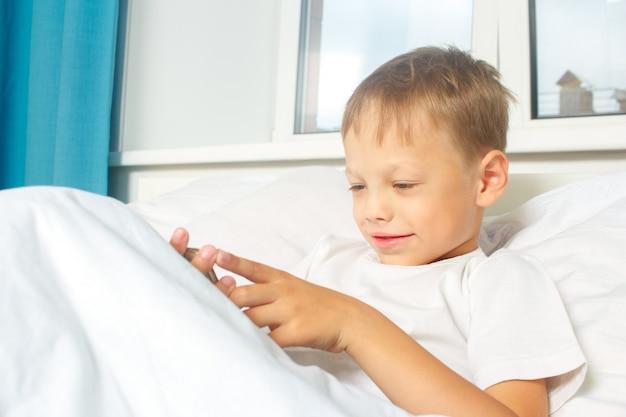 Un bambino di sei anni si riposa sdraiato nel letto e tiene in mano uno smartphone. un bambino con un gadget a casa.