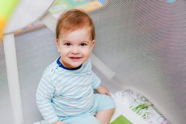Un bambino di un anno è seduto in un'arena
