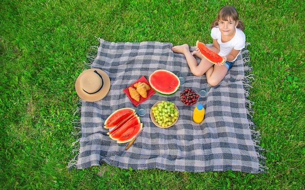 Un bambino durante un picnic mangia un'anguria