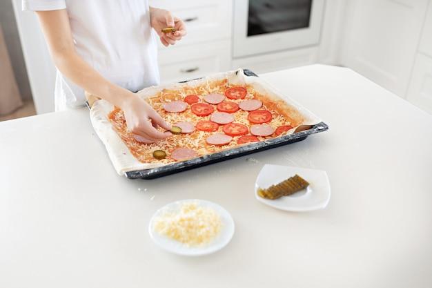 Un bambino fa una pizza. salame, formaggio, ketchup, pomodori, cetrioli.