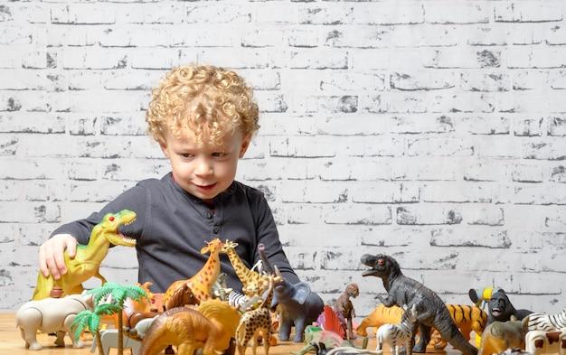 Un bambino gioca con animali giocattoli