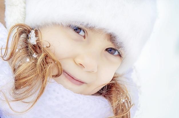 Un bambino gioca nella neve in inverno. messa a fuoco selettiva