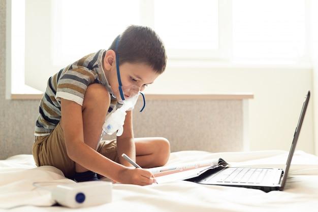 Un bambino impara le lezioni a casa in una maschera d'ossigeno con un nibulizer, un computer portatile e un libro