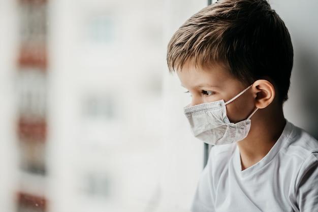 Un bambino in maschera medica è seduto a casa in quarantena a causa del coronavirus e della covide -19 e guarda fuori dalla finestra.