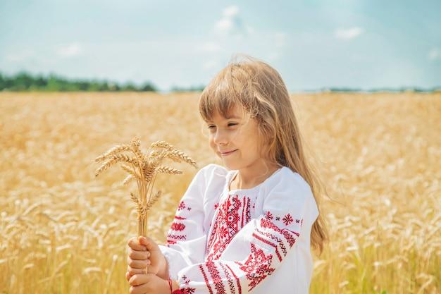 Un bambino in un campo di grano in una camicia ricamata.